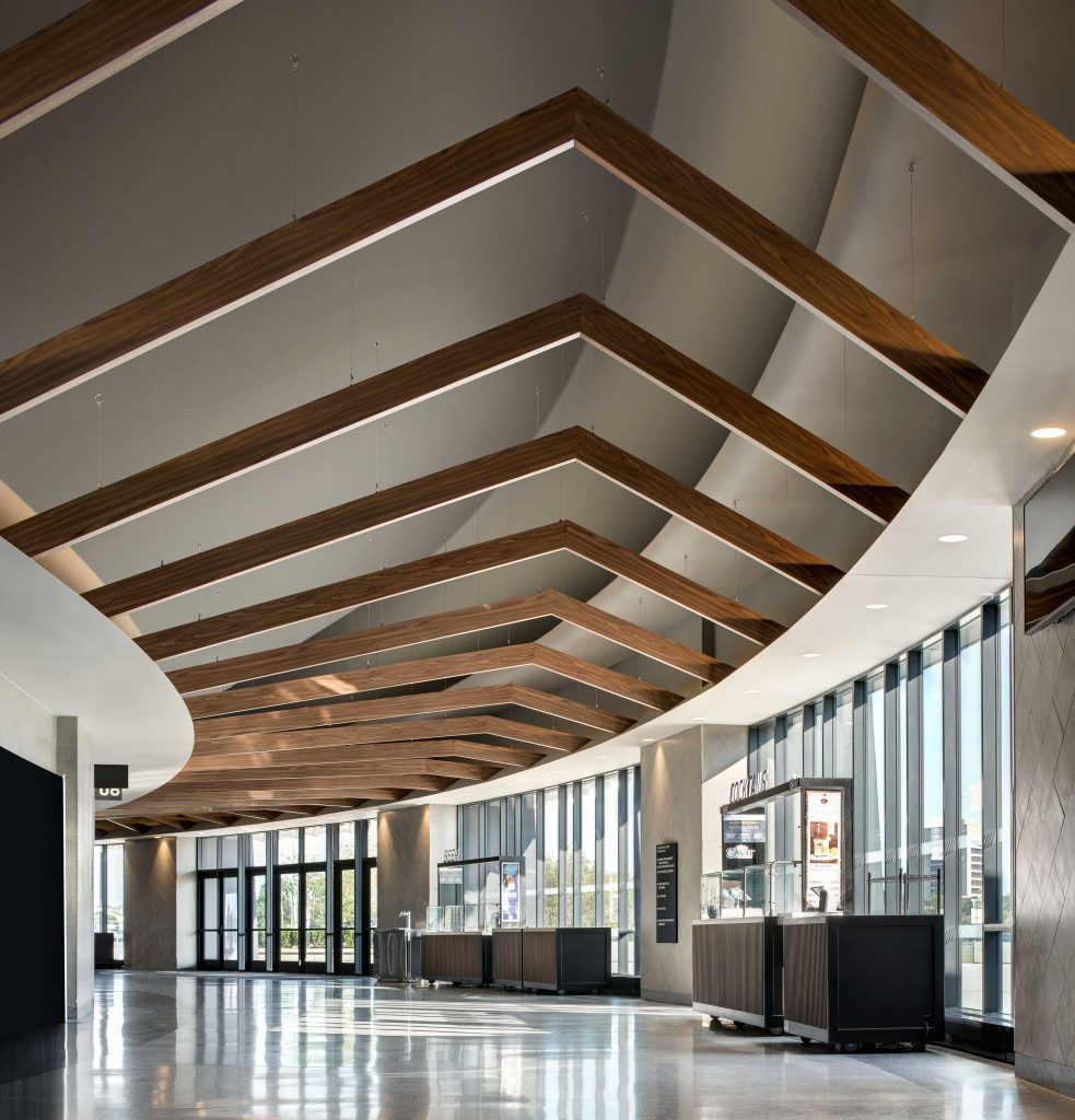 Peaked metal beams with a decorated wood look finish lead visitors through the curved concourse into the bowl.