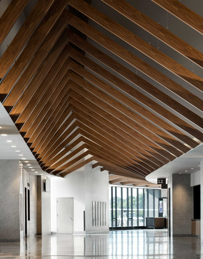 "Here, Hunter Douglas' engineering team worked to design each beam's length and angle, varying each to establish a visual ""wave effect."""