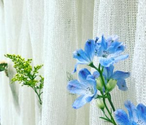 Real flowers are tucked into slight pockets on hanging, washable fabric which uses thread made from paper.