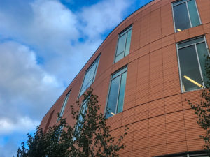 The standout façade features glass with profiled NBK terracotta panels in natural shades of an orange-red finish.